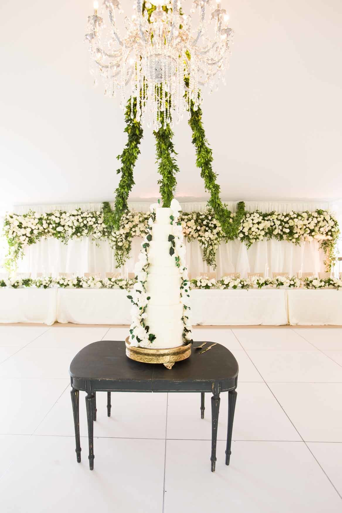 White wedding cake on table beneath a crystal chandelier and green garlands