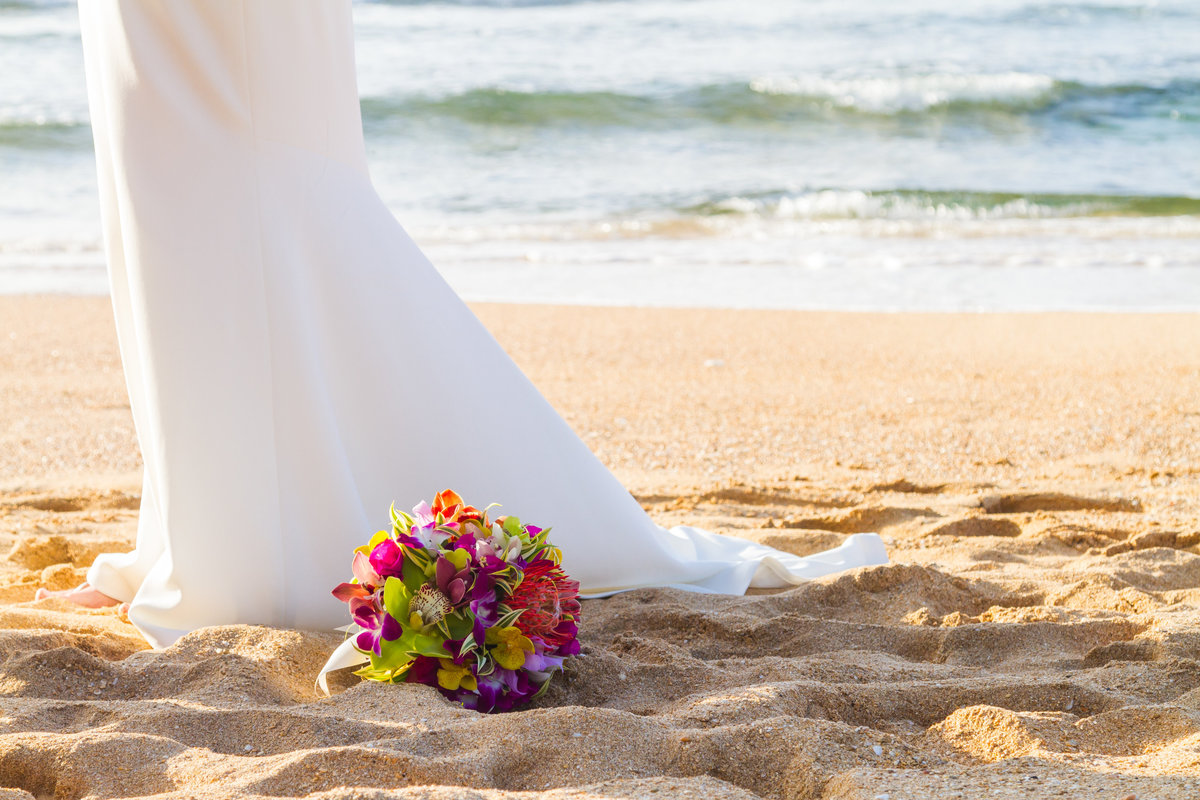 Colorful tropical wedding bouquet with bridal gown on the beach in Kauai.