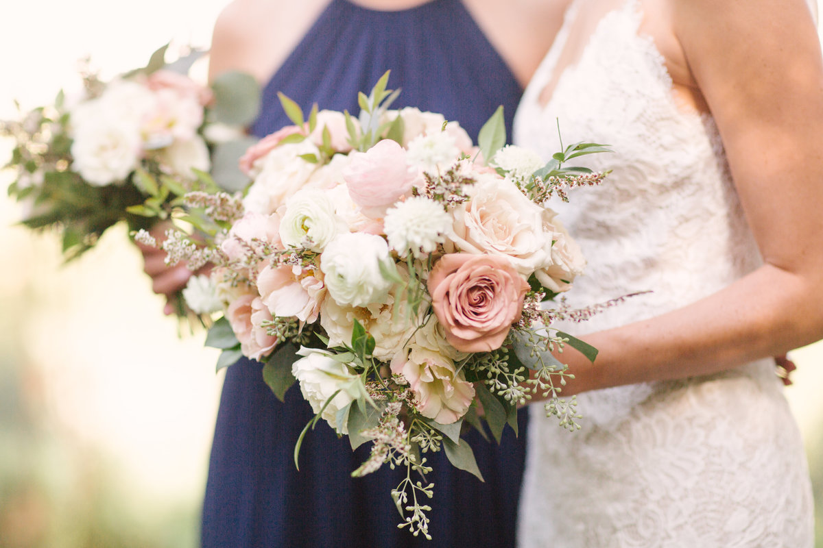 Bride and bridesmaid hold bouquets at Firestone Vineyard wedding