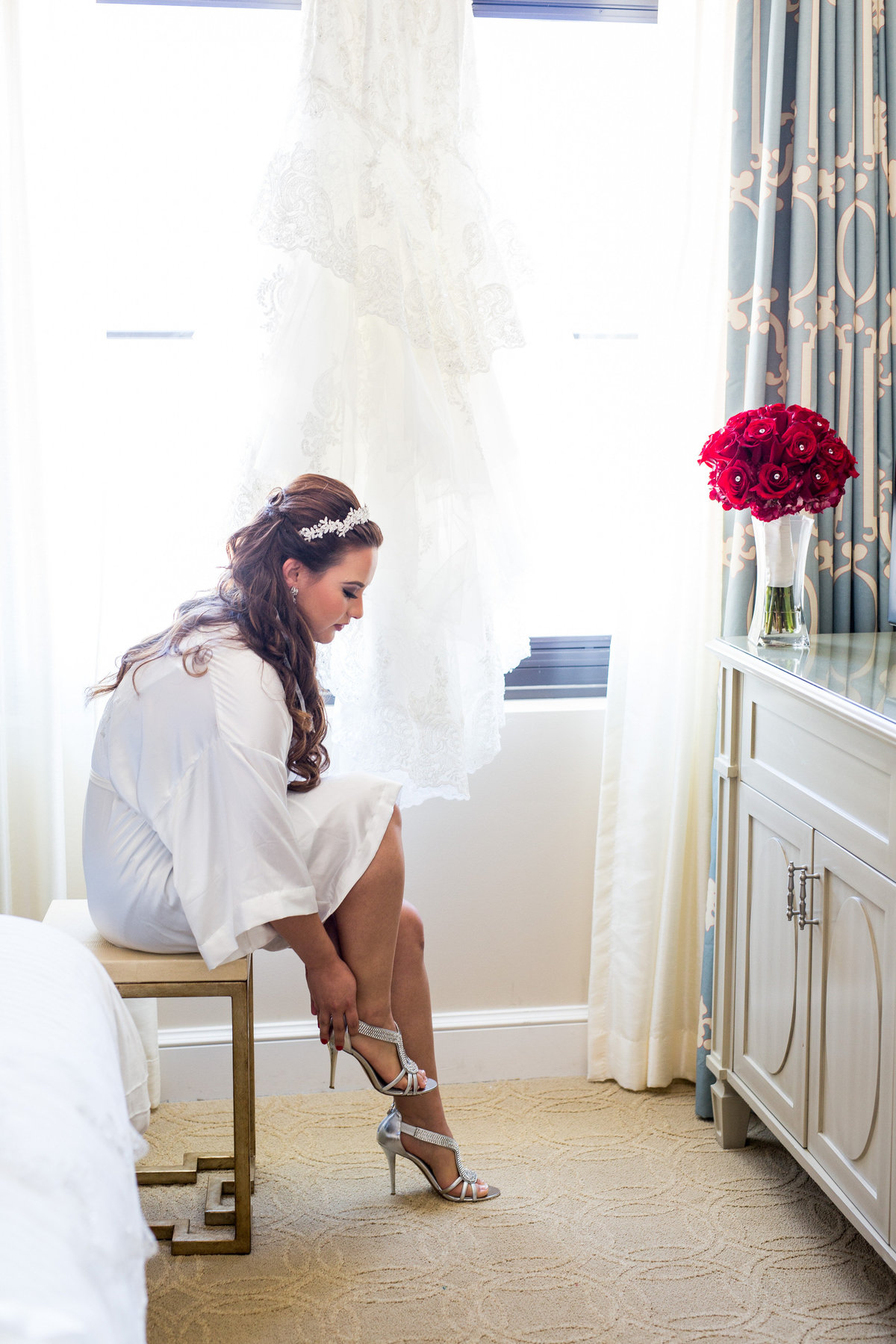 Bride putting her wedding shoes on as she gets ready for wedding ceremony at Eilan Hotel