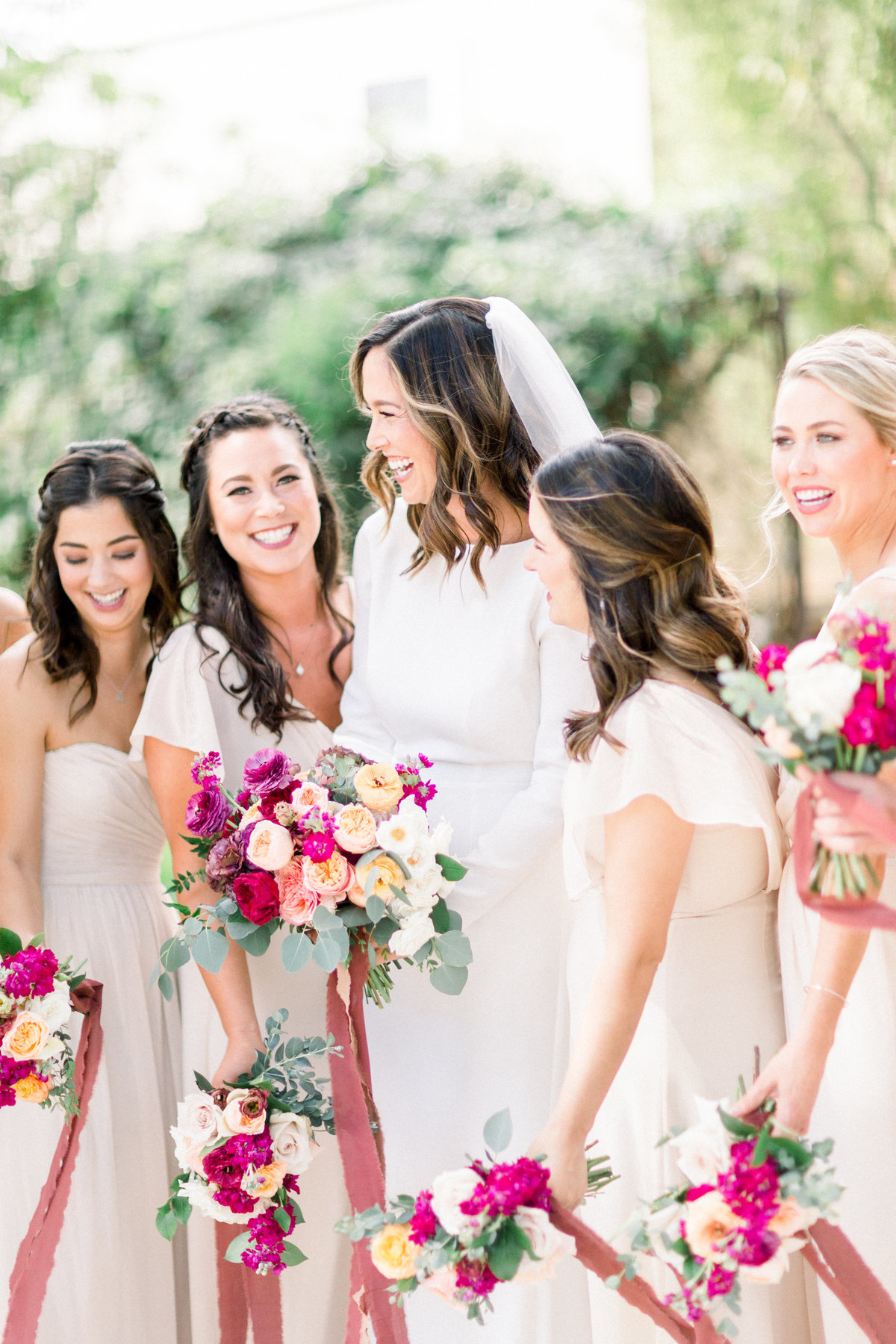 bride in long sleeve white dress with bridesmaids in neutral dresses with mauve bouquets wrapped in ribbon at Maravilla Gardens wedding