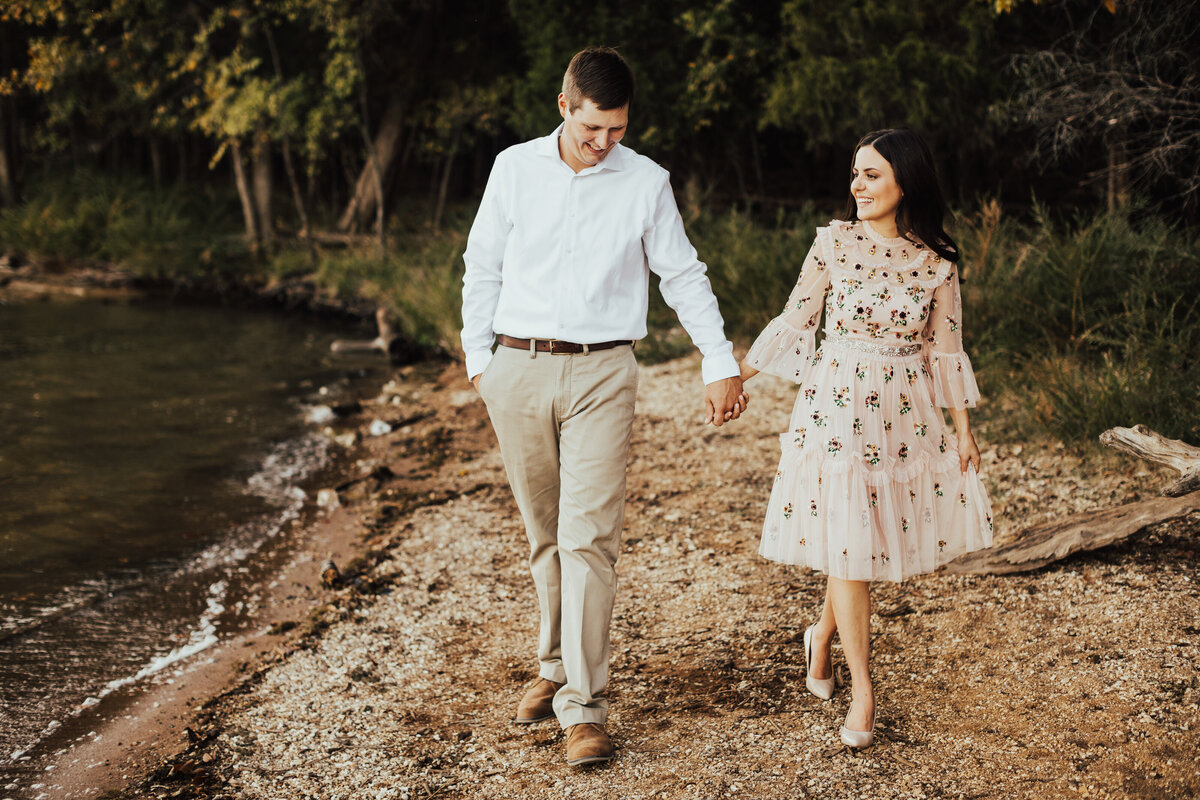 couple holding hands walking next to water