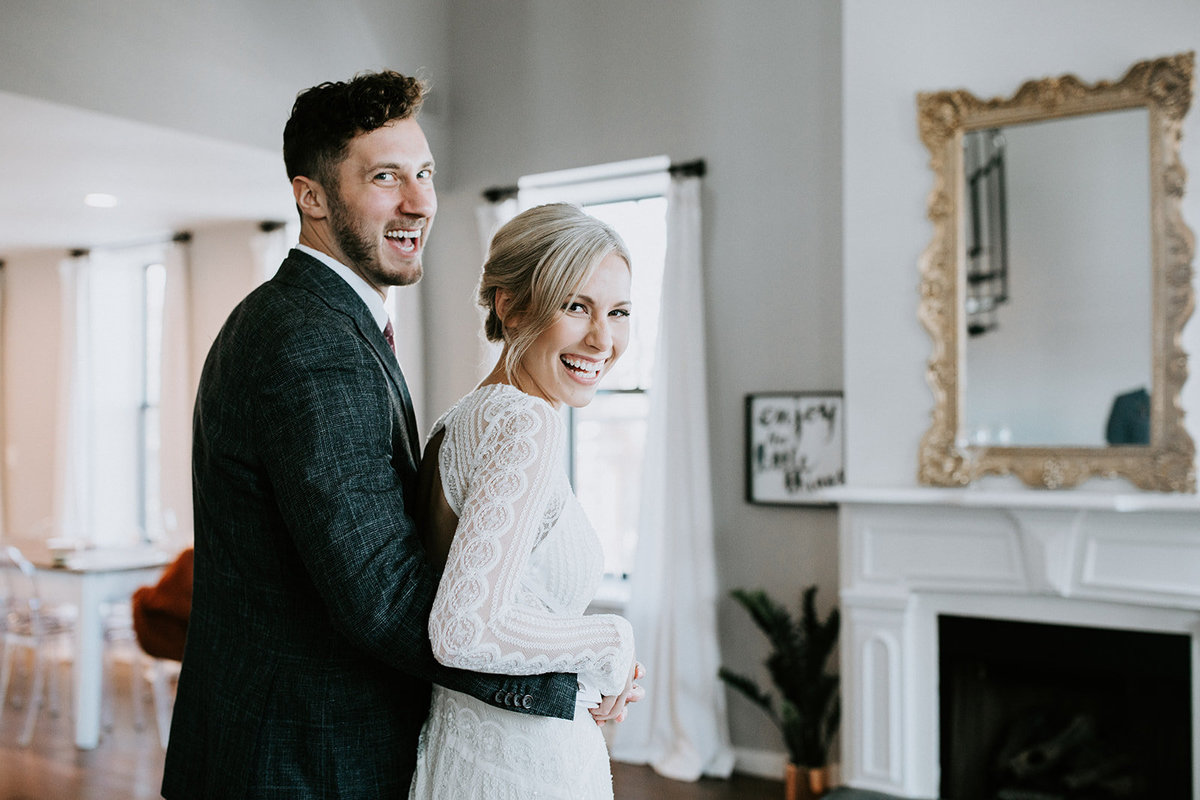 A bride and groom smile in front of a fireplace.