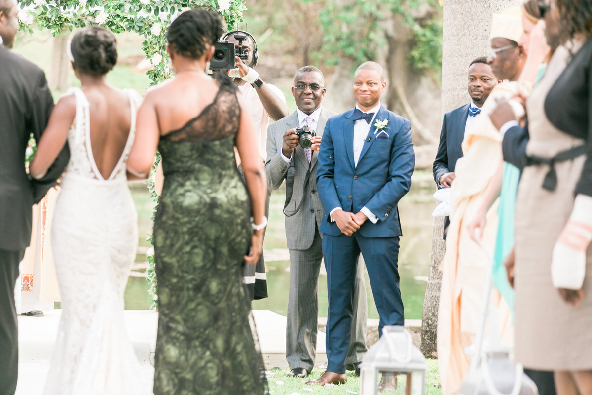 Guest stands next to groom to take a photo of bride walking down aisle