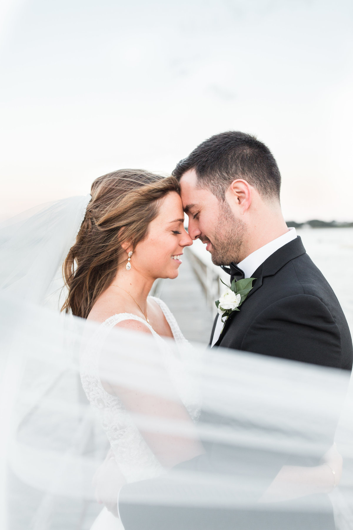 Bride and Groom touching foreheads with windswept veil