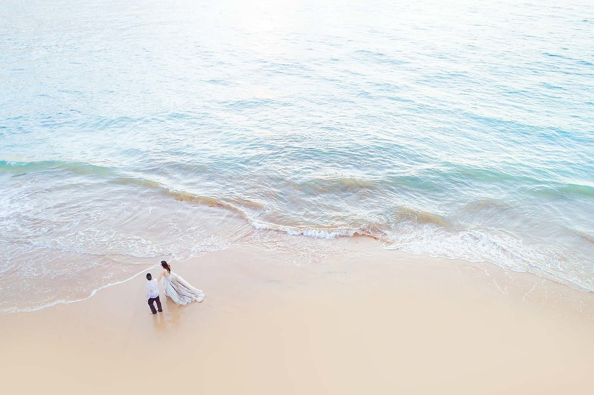 Husband and wife walk on the beach on Maui with pastel water