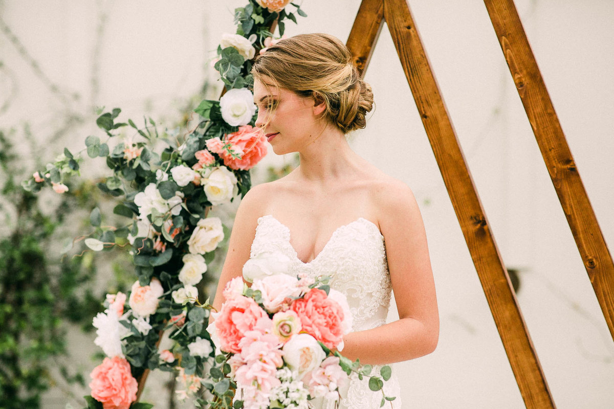 Bride in front of flower adorned wooden arch