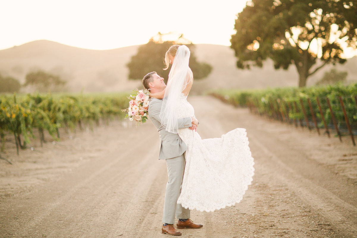Groom lifts bride at Firestone Winery wedding