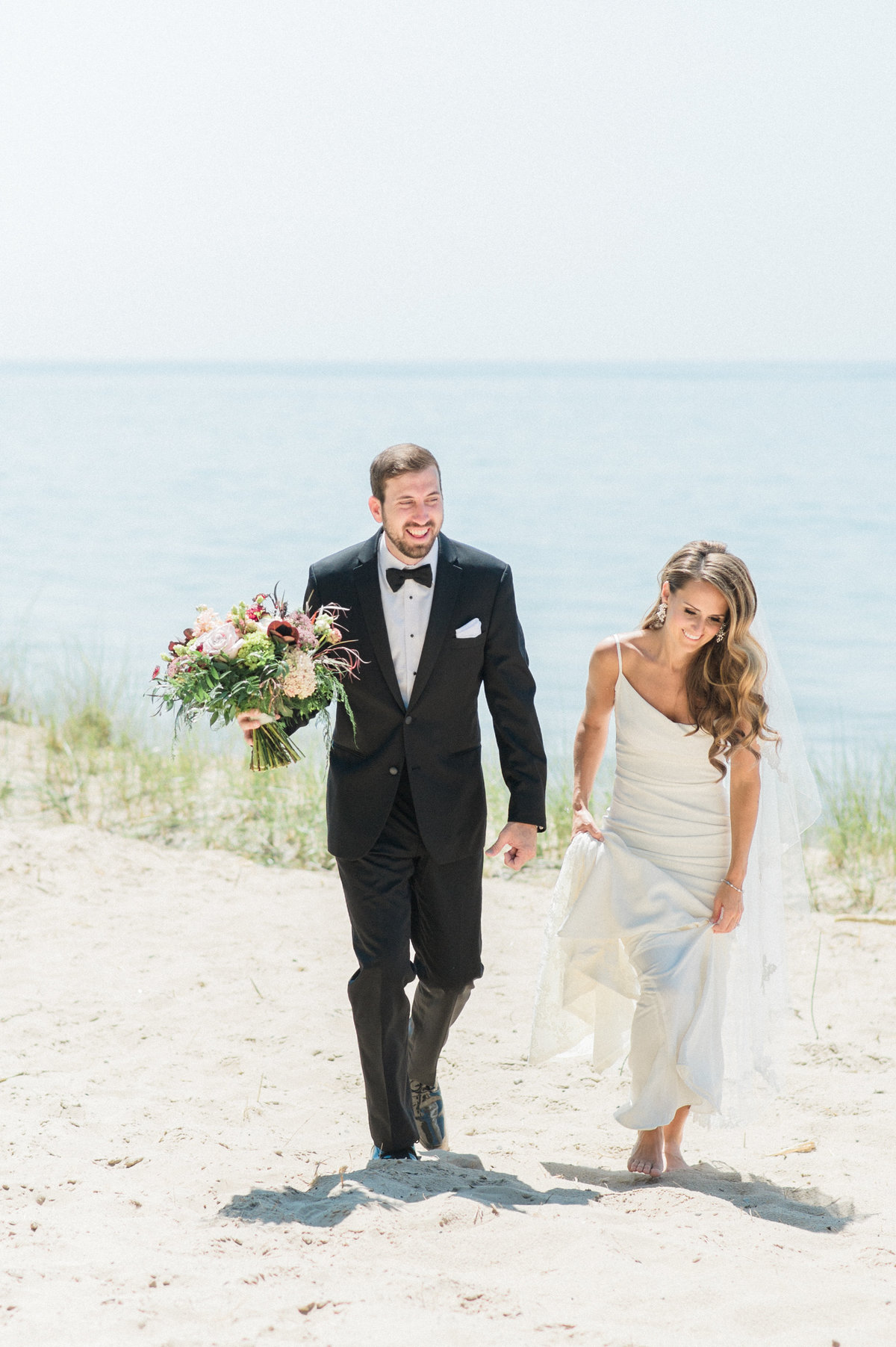 bride and groom smiling walking on beach