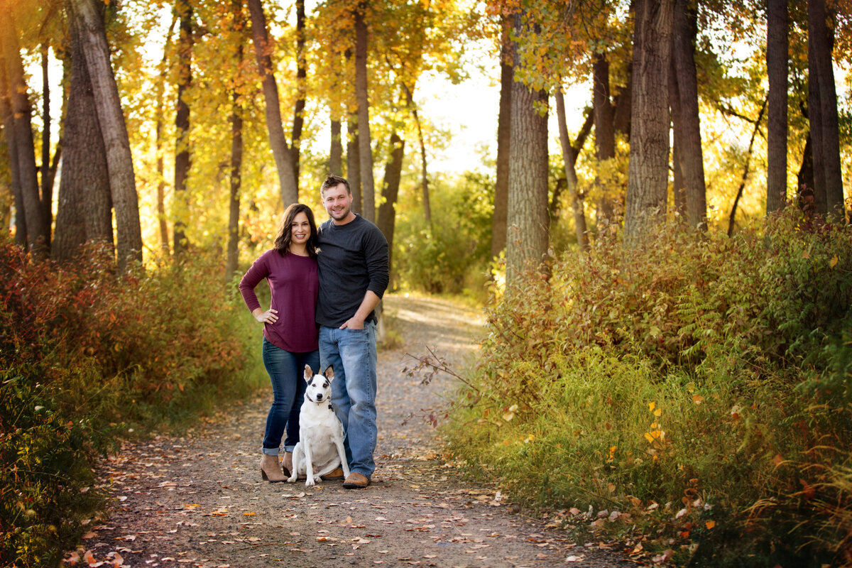 picture of couple and a dog at river front park located in billings montana, standing in tree covered path with their white pet dog. Fall colors, jewel toned clothes. family photographer in billings mt,