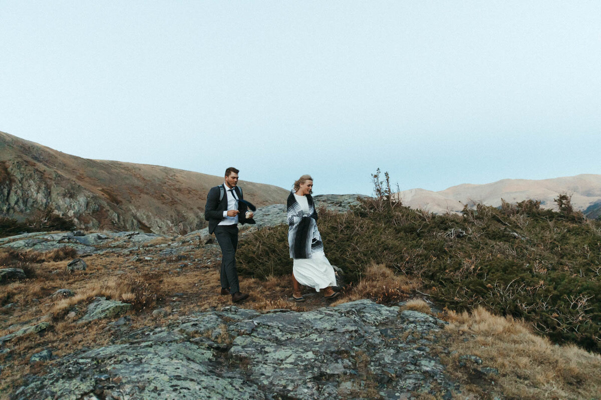 A woman and man hike in the mountains wearing a suit and a wedding dress, respectively,
