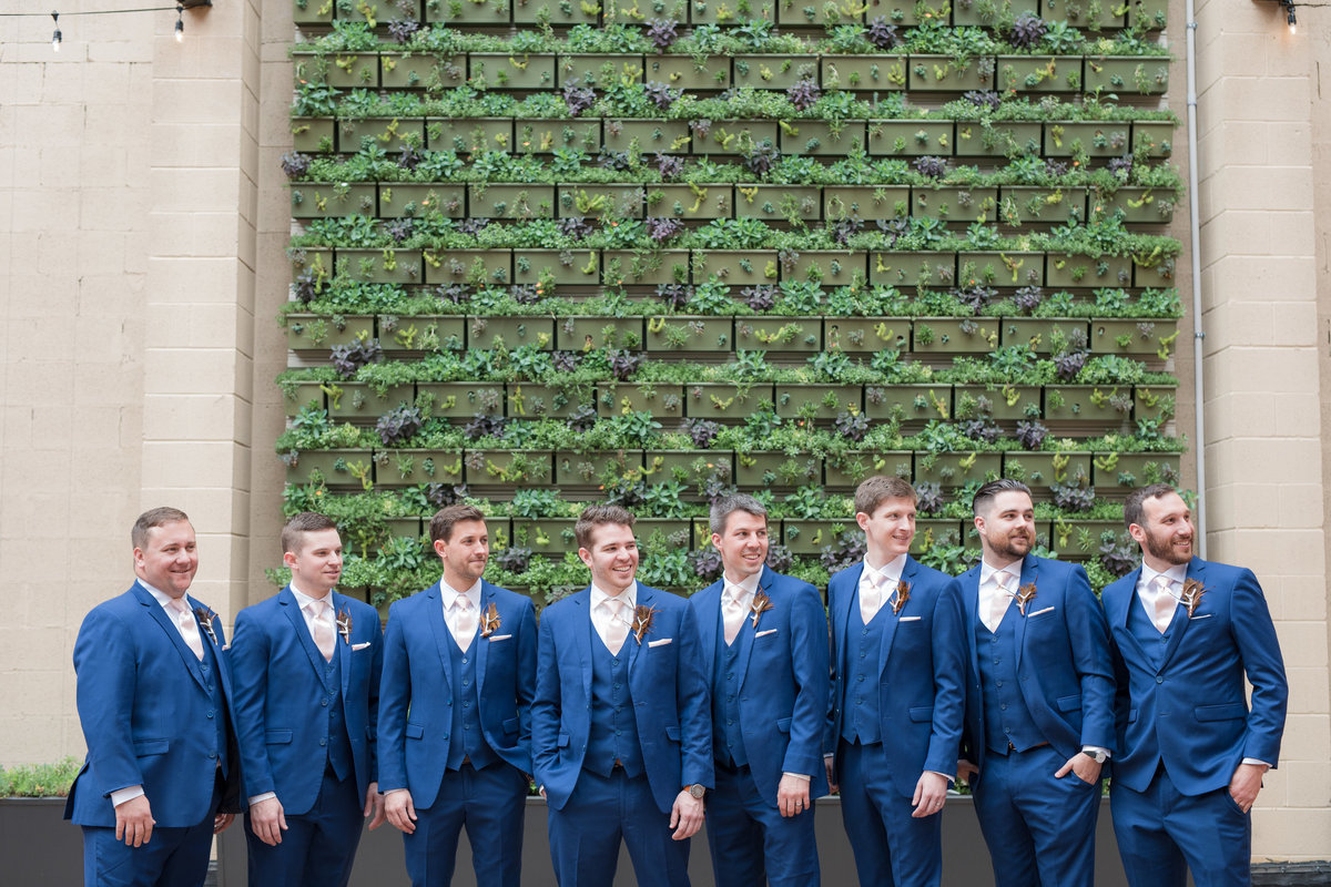 Groom and groomsmen by  the green wall at Excelsior Lancaster