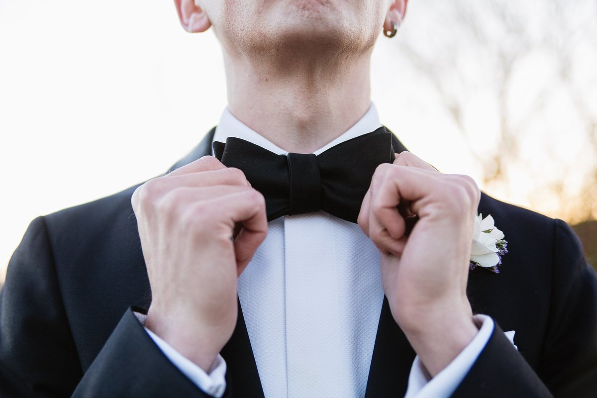 Groom adjusting his bow tie on his tux by Phoenix wedding photographer PMA Photography.
