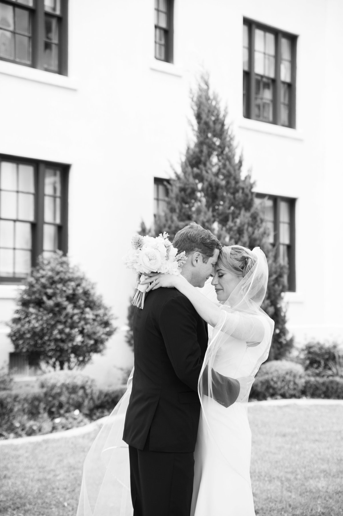 Romantic moment with bride and groom at the white house hotel in biloxi while bride holds bouquet and wears cathedral veil