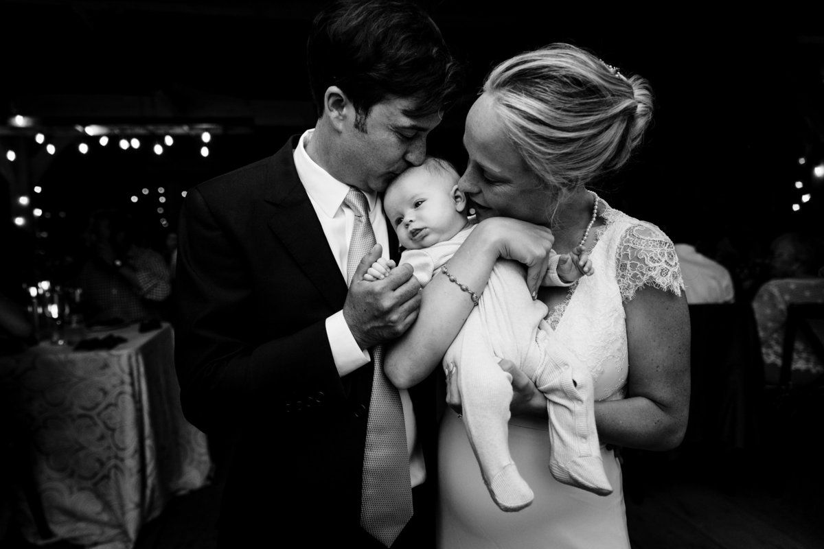 Primo Restaurant Wedding with the bride and groom kissing their newborn daughter at their intimate wedding celebration in the barn