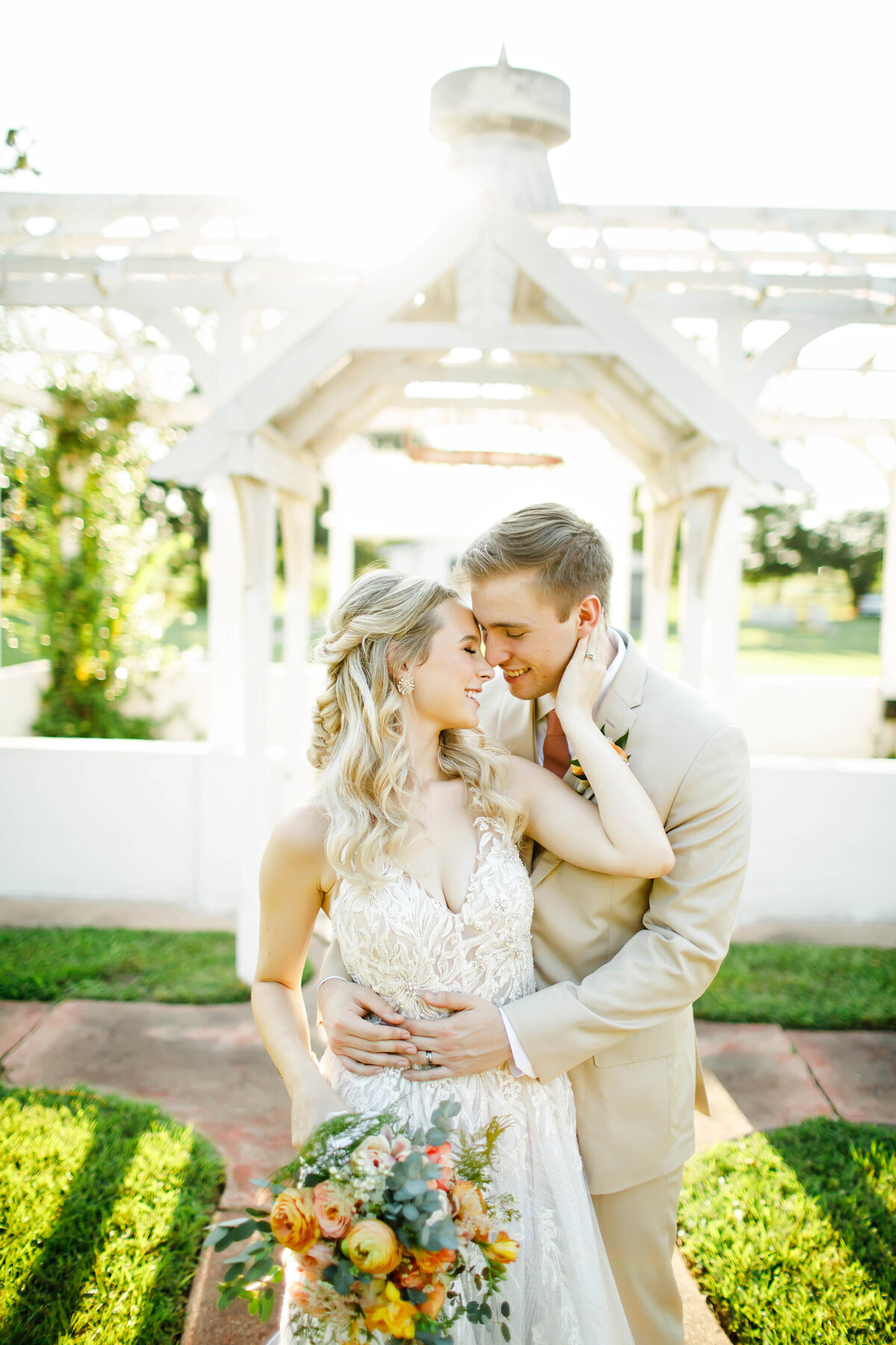 A beautiful bride and groom on wedding day. Standing in front of the Greenhouse Arbor at the Grand Texana. The bride is leaning into the groom and holding her bouquet