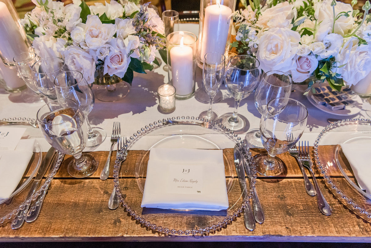 a rustic tablescape with silver beaded charger plates and white floral centerpiece with white candles
