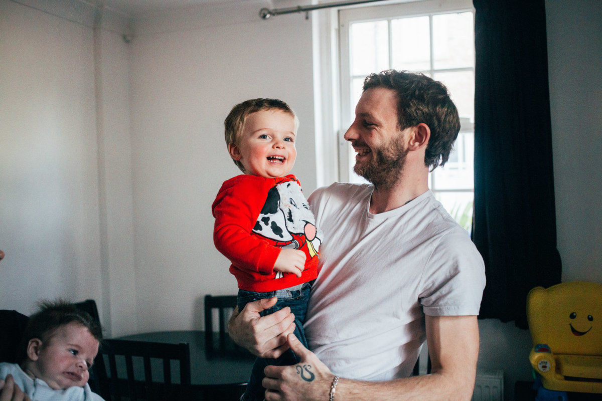Relaxed family photo of ipswich dad holding his son wearing red