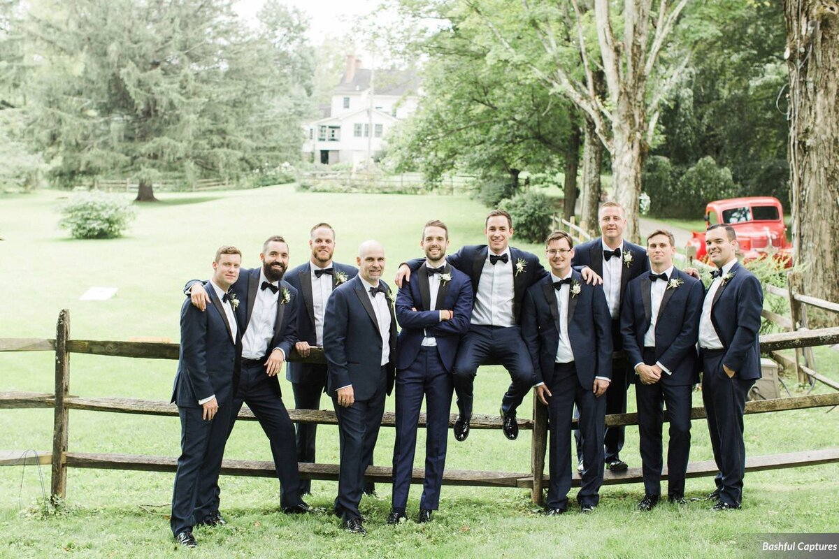 Grooms party gathers around groom leaning on fence on estate grounds