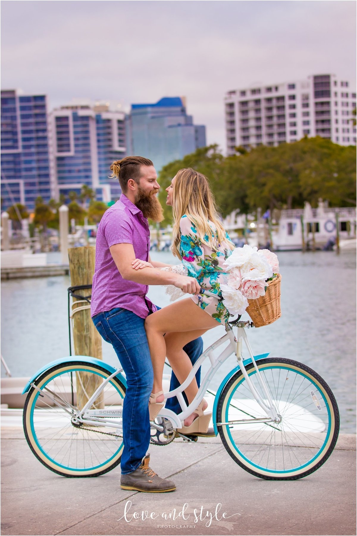 Sarasota Engagement Photography of couple on a blue bike kissing in Bayfront Park