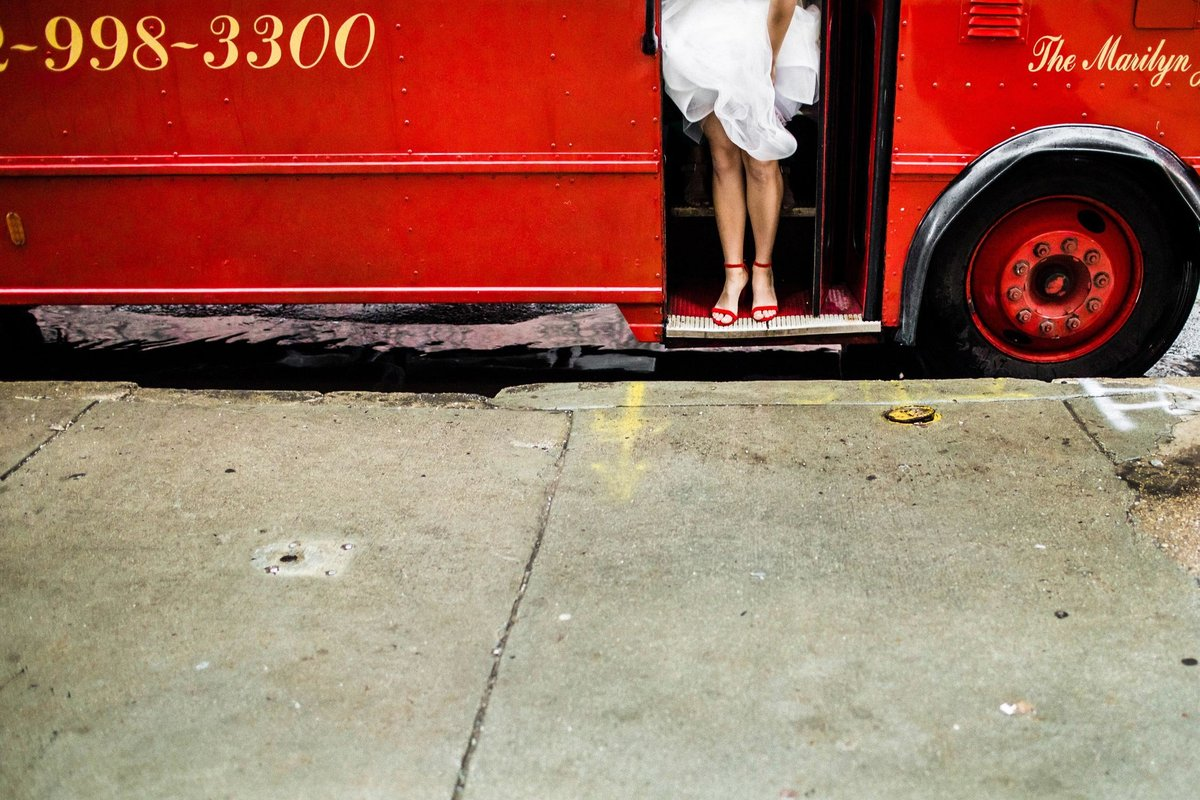 A bride in red shoes exits a trolley before a Carnivale wedding.
