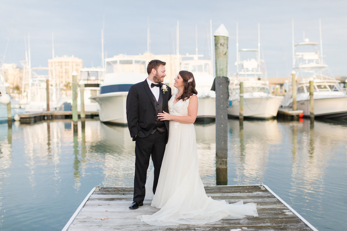 Bride and Groom smiling at each other  by the boats at The Water Table