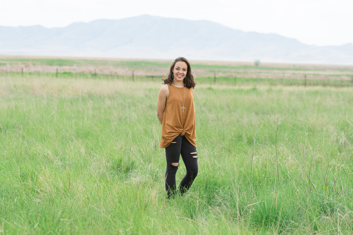 senior girl stands in grassy field during senior session in syracuse utah
