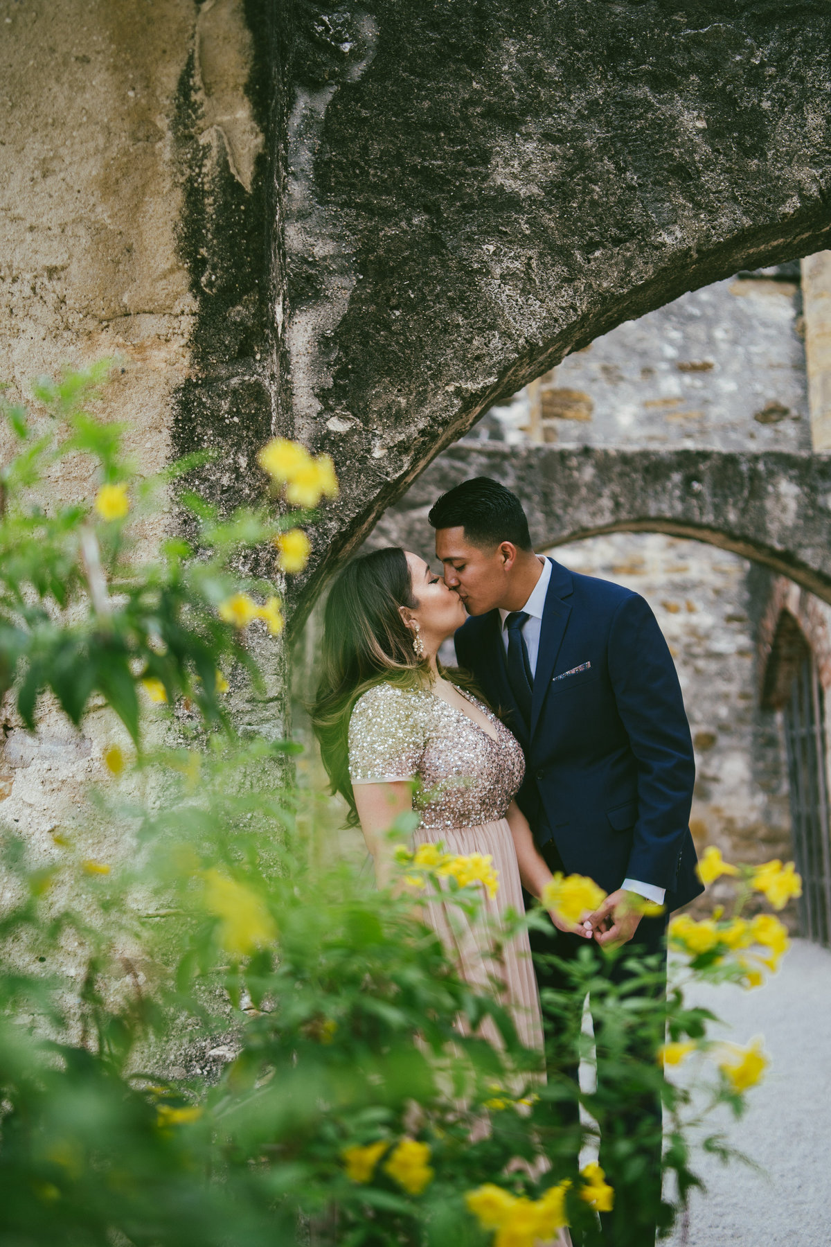 Engaged man and woman kissing behind yellow flowers and under an arch at Mission San Jose in San Antonio, Texas.