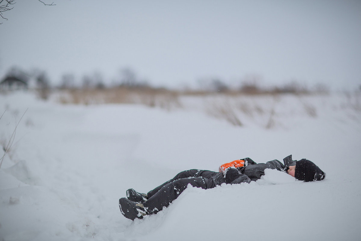 child laying in snowbank in rockford illinois