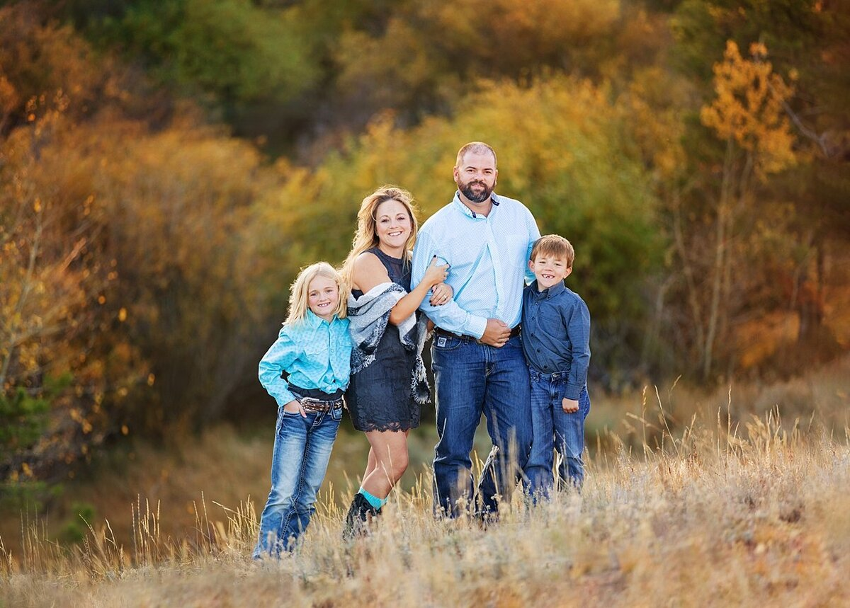 A family picture session by laramie in front of beautiful fall leaves.