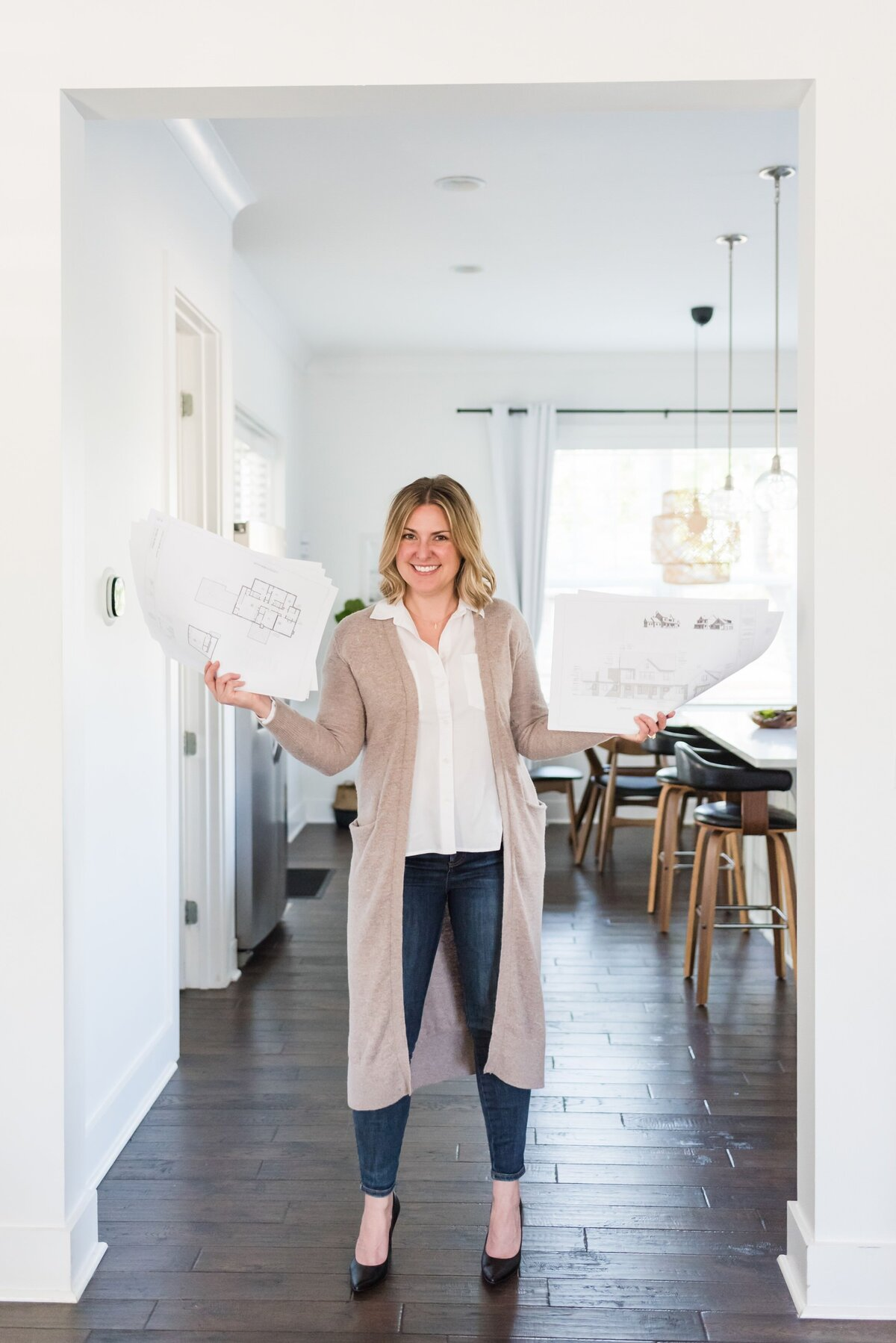 Nashville realtor and architect standing in doorframe with building plans in her hands for a headshot