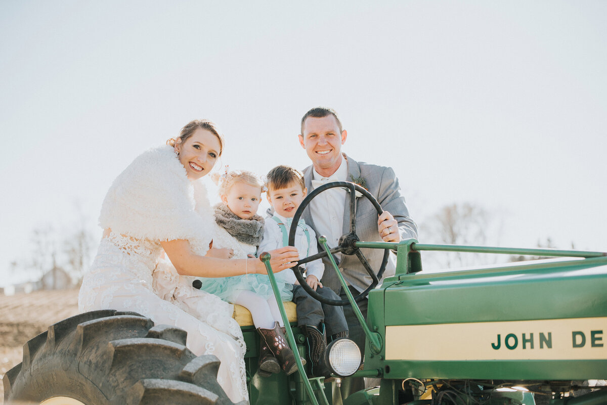 bride and groom pose with john deer tractor in iowa