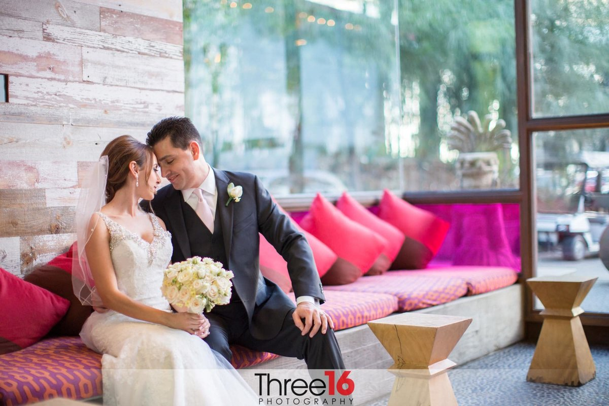 Bride and Groom sitting on a couch enjoying the moment together
