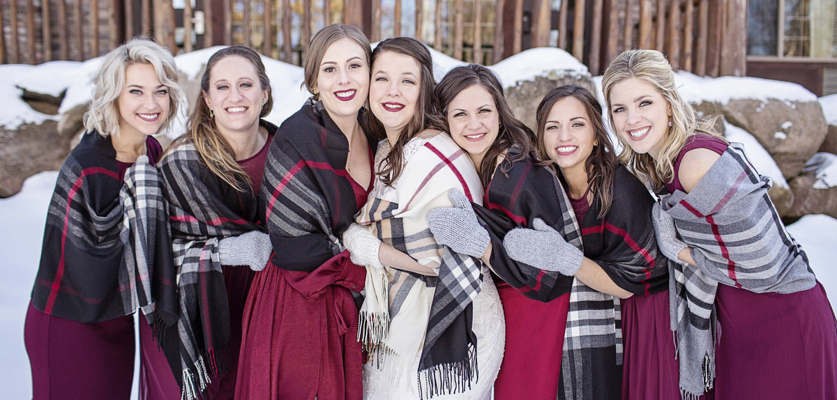 Bridesmaids in winter wedding in Minnesota and Wisconsin wearing deep red. bridesmaids in scarfs.
