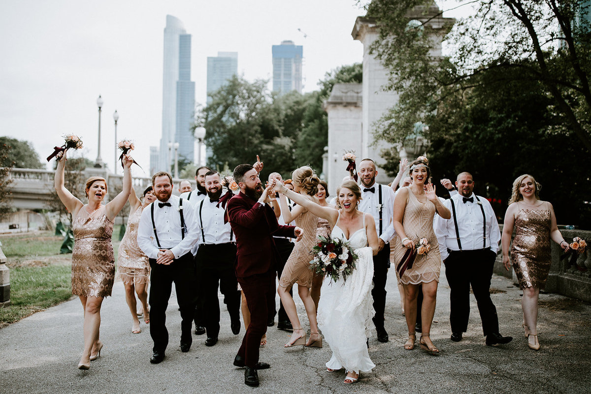 A wedding party dancing in the park.