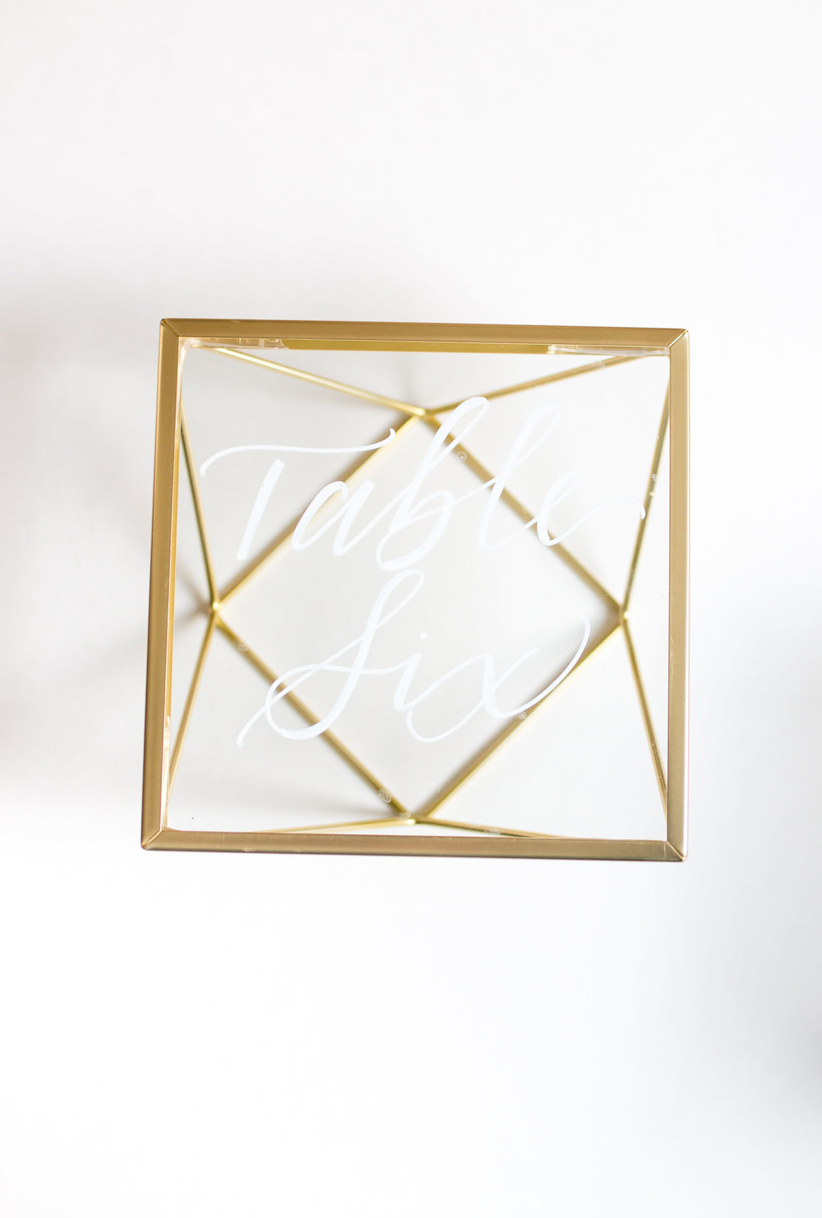 Geometric glass table number with white calligraphy for weddings or events rental through Hue + FA Rentals