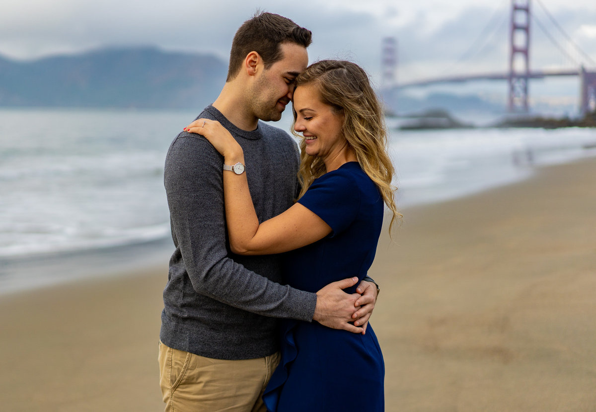 Beach engagement session with couple holding each other