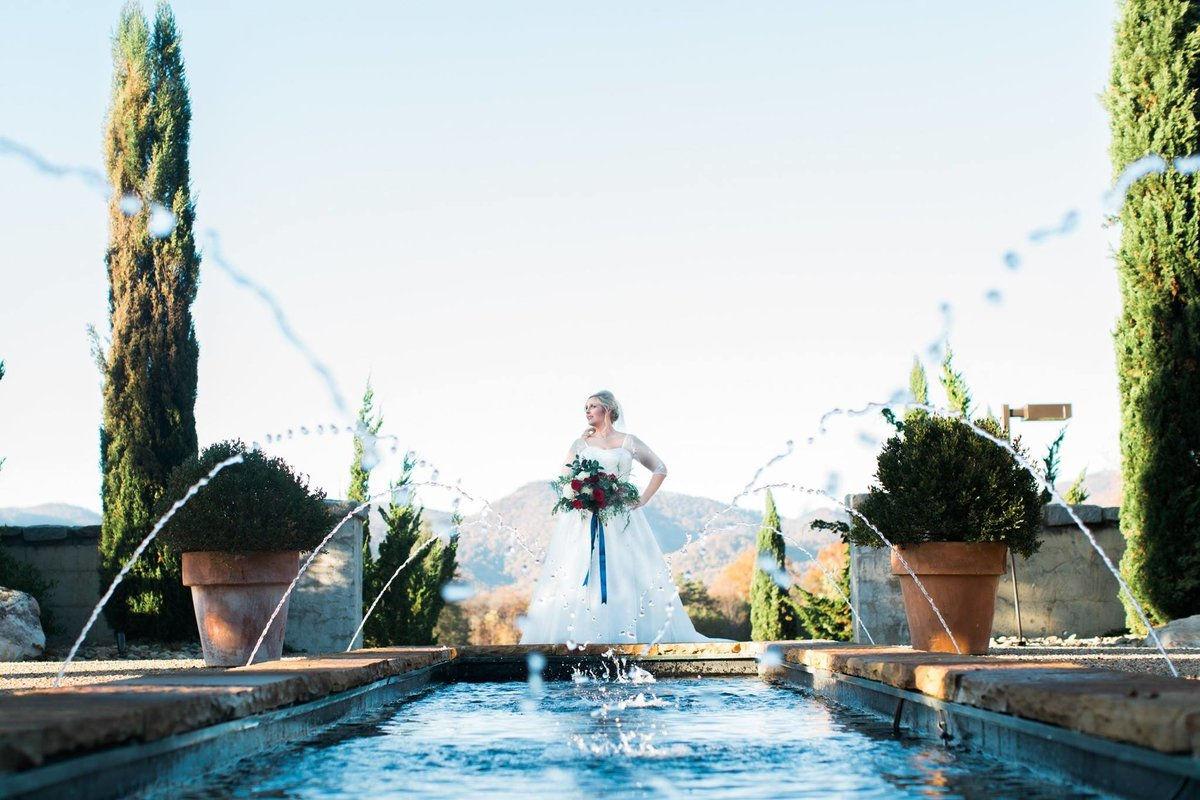 Wedding Photographer, bride standing next to pool and fountains