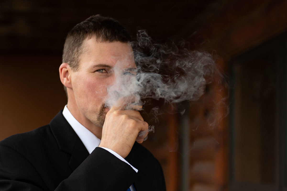 guest steps out for cigar pic with smoke