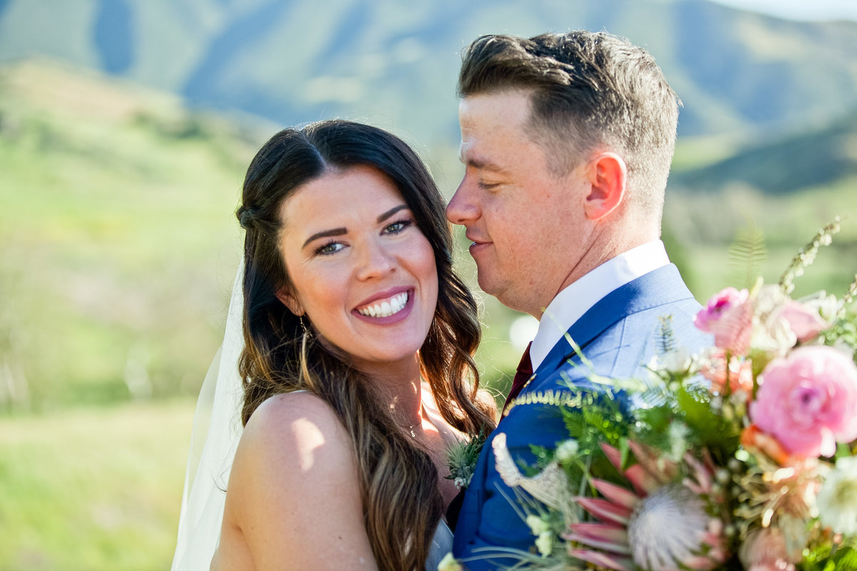 Romantic Spring Elopement  bride and groom in field with Spring bouquet at Higuera Ranch  in San Luis Obispo  by Amy Britton Photography Photographer in St. Louis