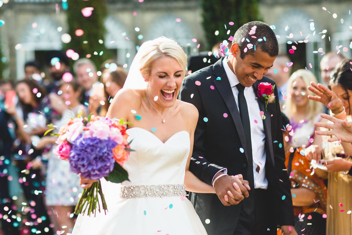 confetti thrown at bride and groom outside sezincote house