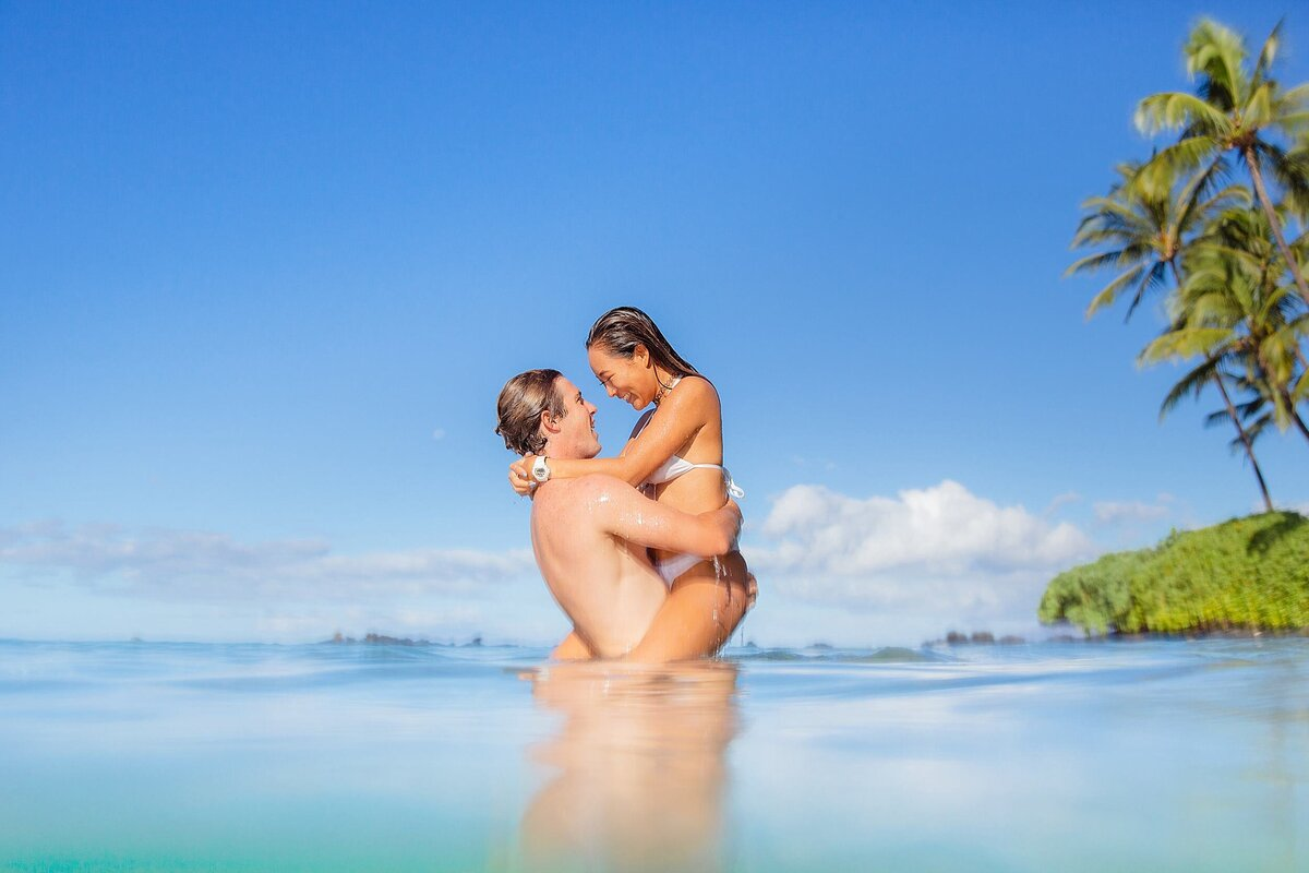 Man holds woman in the water at White Rock Beach on Maui