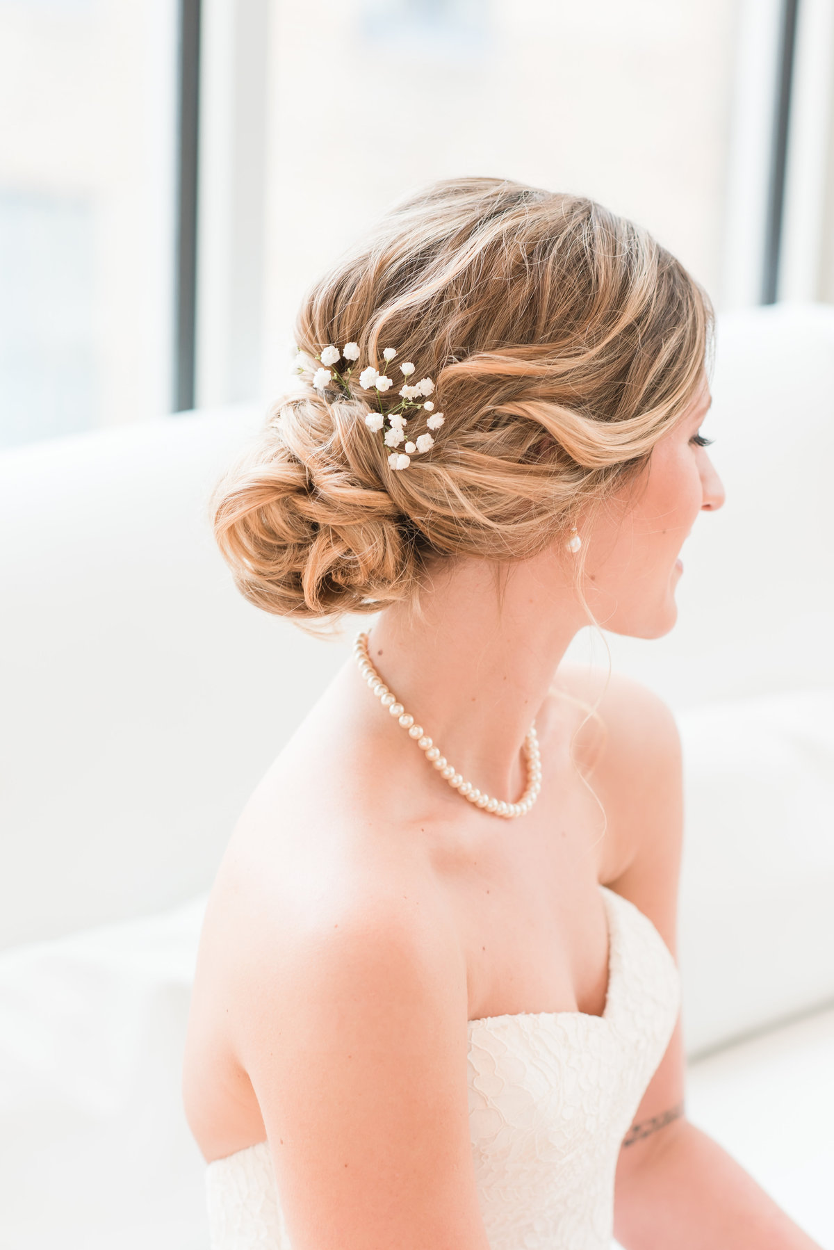 A bride sitting on a white couch wearing a strapless dress looking down with the focus on her updo hair with babies breath at the Glass Box at 230