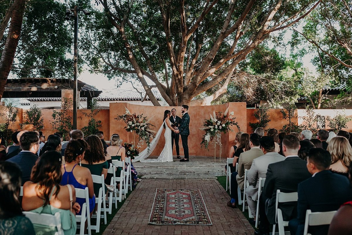 Bride and Groom stand at the center of the altar sharing their vows under a large tree with guests watching