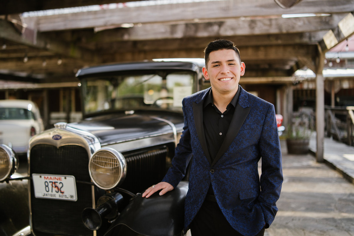 high school guy posing with classic car in San Antonio by high school senior photographer