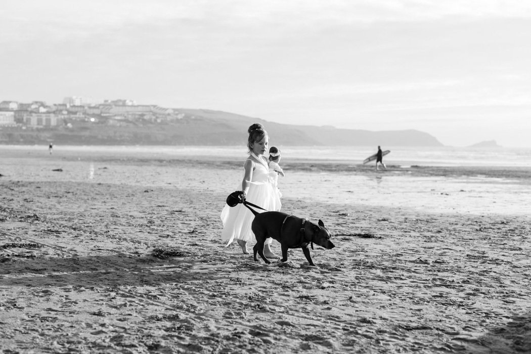 Flowergirl and her dog on the beach at Woolacombe Bay Hotel Wedding
