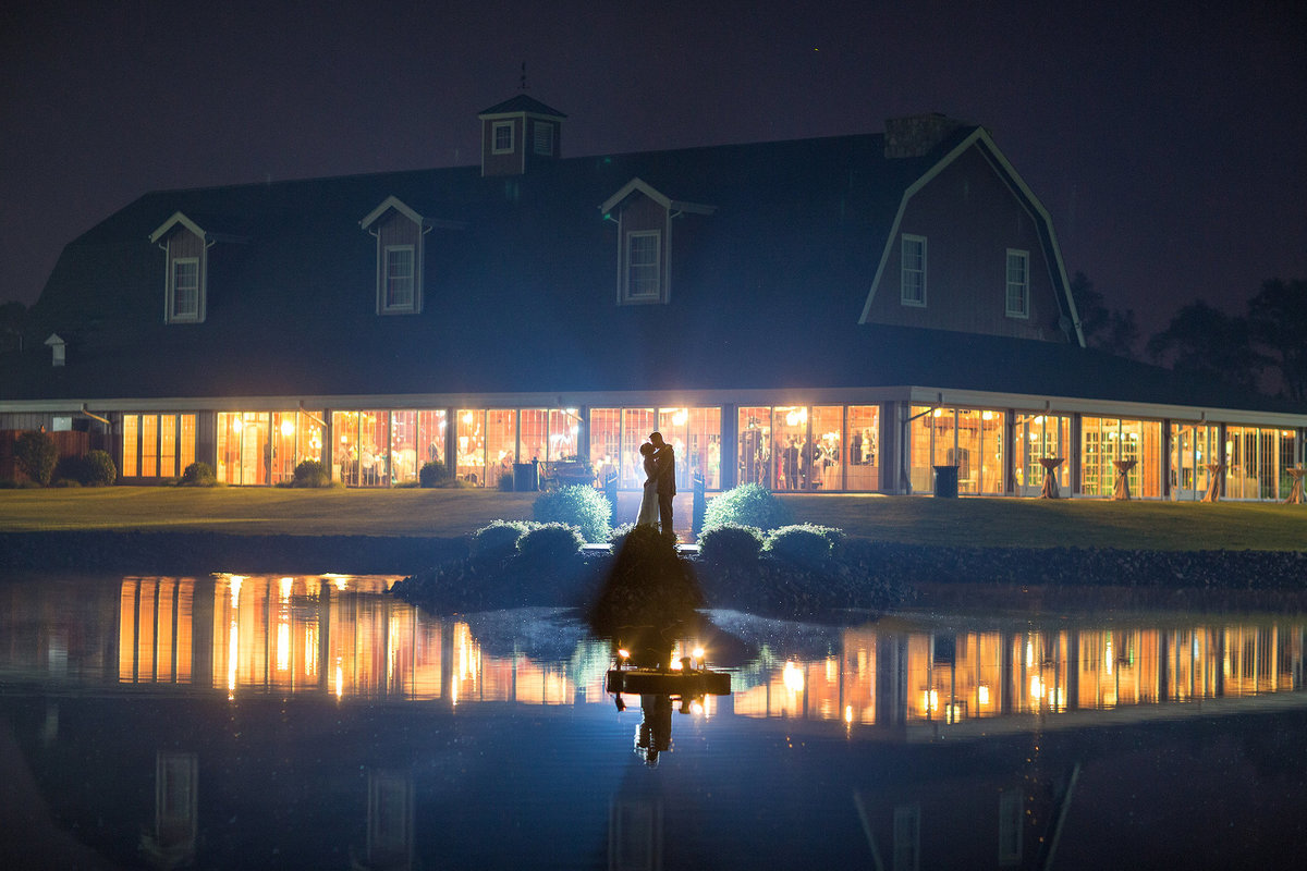 wedding couple kissing at night with pavilion in reflection