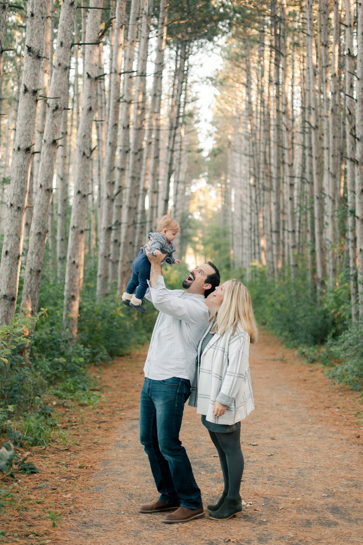 parents of 6 month old baby girl play in the pine forest of twin cities minnesota