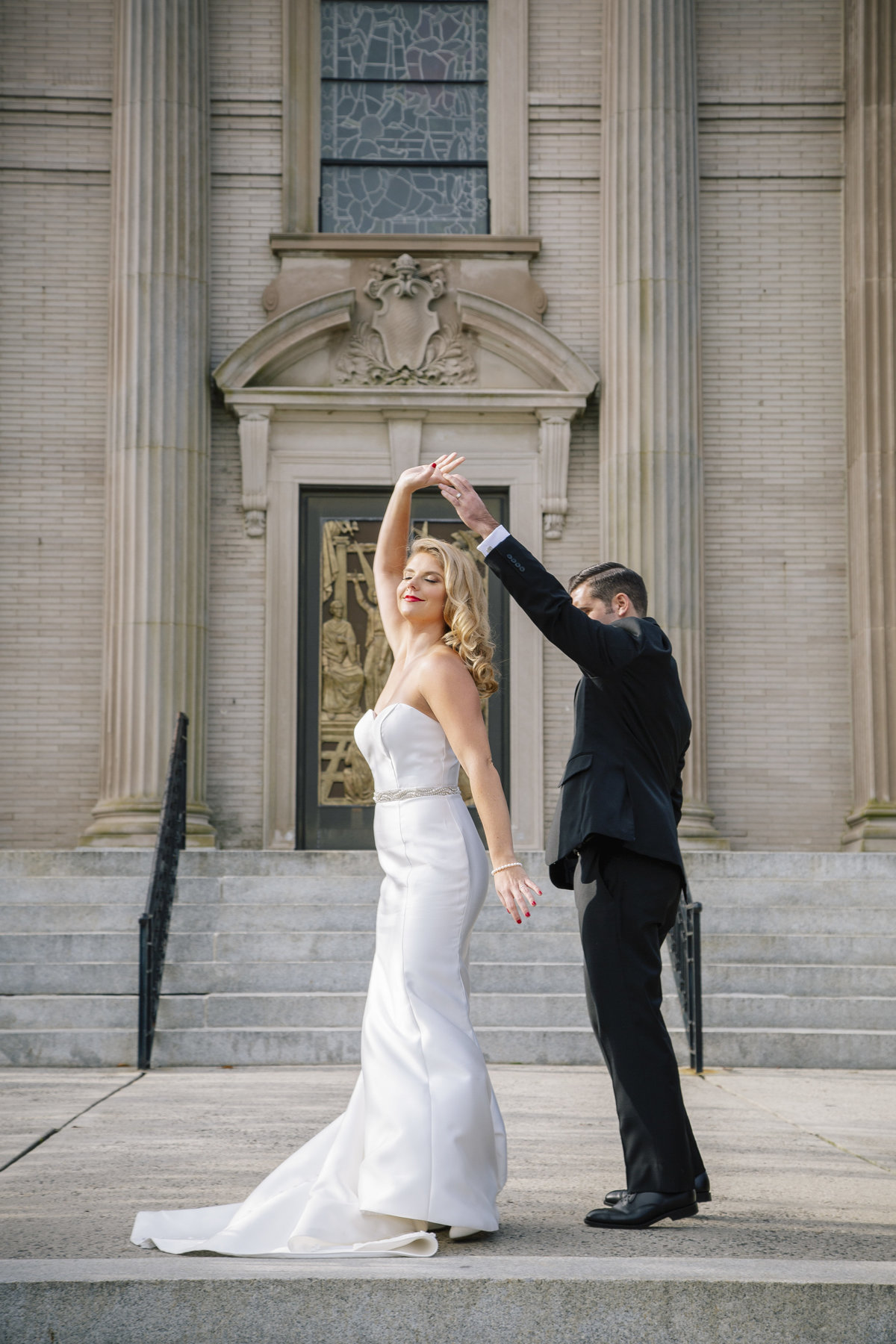 bride and groom dancing outside saint catharines church before spring lake wedding
