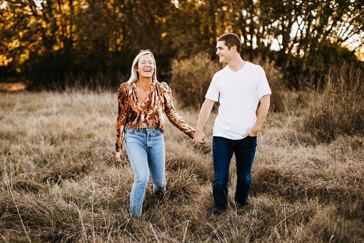 couple holding hands laughing in field at golden hour